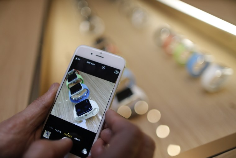 Image: Customer using iPhone to take pictures of the new Apple Watch