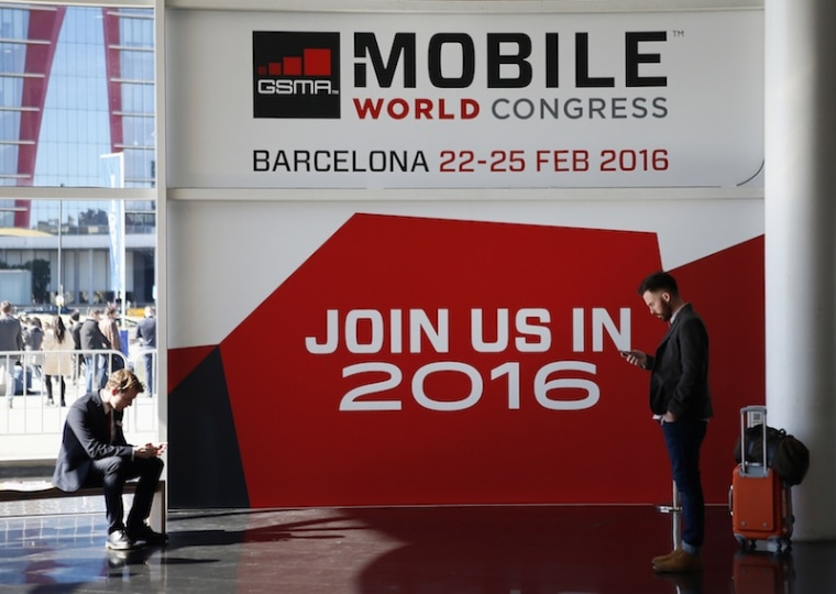 People look at their mobiles in front of the 2016 Mobile World Congress edition banner in Barcelona