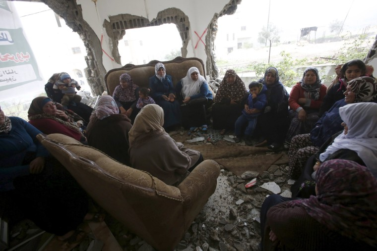 Image: Palestinians gather in the home of Mohammed al-Haroub after it was partially demolished by Israeli army in the West Bank village of Dir Samt