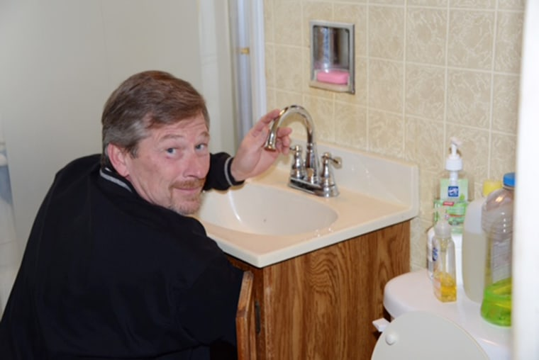 Harold Harrington installs a new faucet to accommodate a water filter in a Flint home.