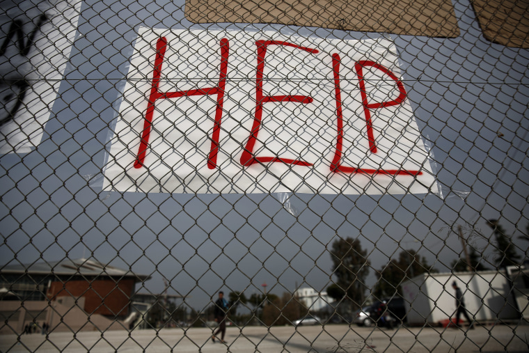 A placard is hung on a fence as migrants make their way inside the premises of a former Olympic indoor stadium in Faliro, southern Athens, on Tuesday, Dec. 15, 2015.
