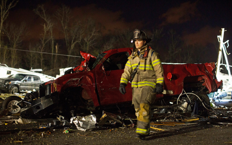 Image: First responders search the remains of trailers and vehicles