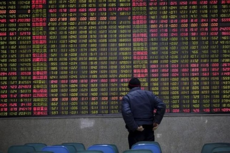 An investor watches an electronic board showing stock information on the first trading day after the week-long Lunar New Year holiday at a brokerage house in Shanghai,