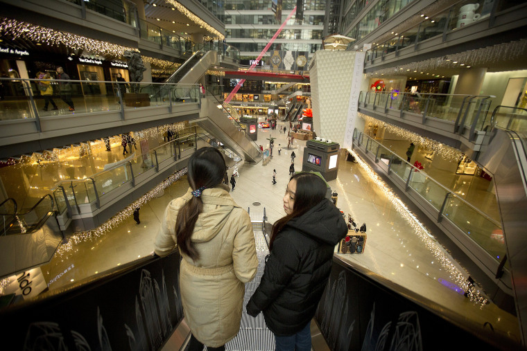 Image: People ride an escalator in an upscale shopping mall in Beijing