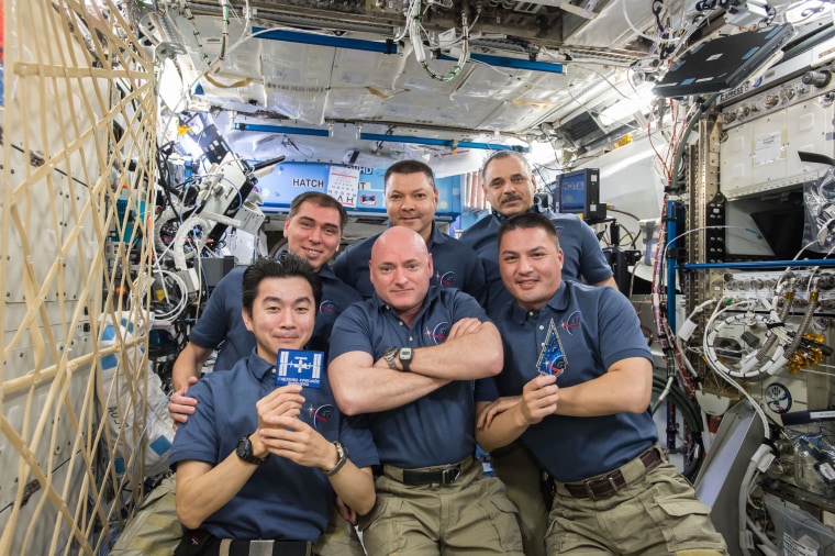 The Expedition 45 crew gathers inside the Destiny laboratory to celebrate the 15th anniversary of continuous human presence aboard the International Space Station on Nov. 2. Front row: Japanese astronaut Kimiya Yui (left) and NASA astronauts Scott Kelly (middle) and Kjell Lindgren. Back row: Russian cosmonauts Sergey Volkov (left), Oleg Kononenko (middle) and Mikhail Kornienko (right). Yui is seen holding the mission patch for Expedition 1 which arrived at the station on Nov. 2, 2000.