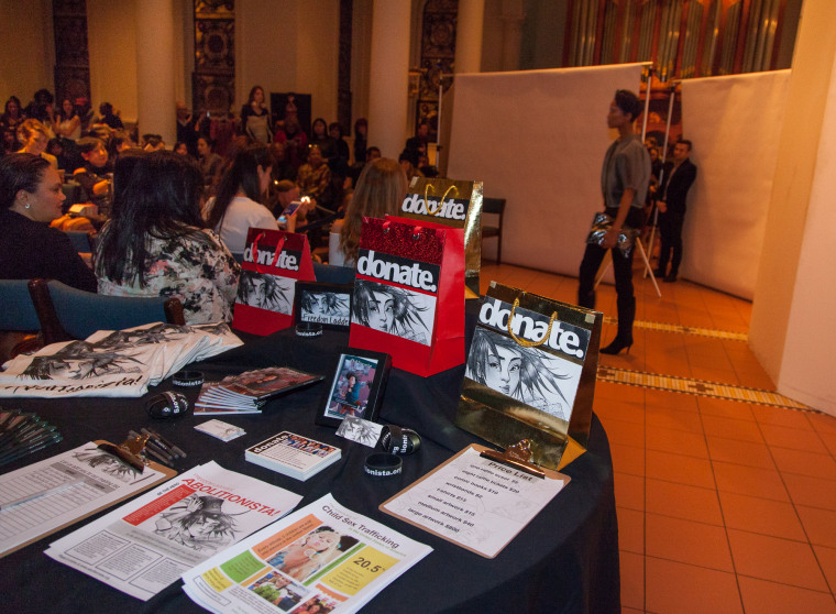 """An informational desk with statistics about sex trafficking and """"Abolitionista!"""" displays at the fashion show."""