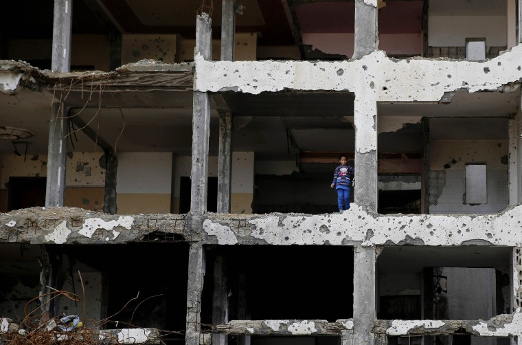 Image: A Palestinian girl stands on a floor of a damaged apartment block