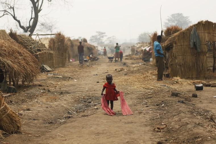 Image: A Christian child walks through a refugee camp in Kaga-Bandoro