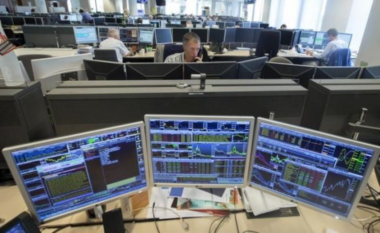 Traders look at screens on the KBC bank trading floor in Brussels