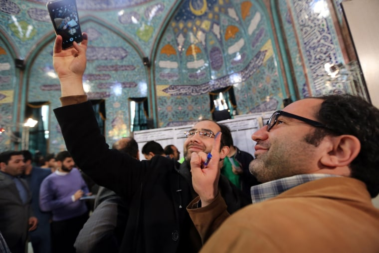 Image: Iranian voters show their ink-stained fingers