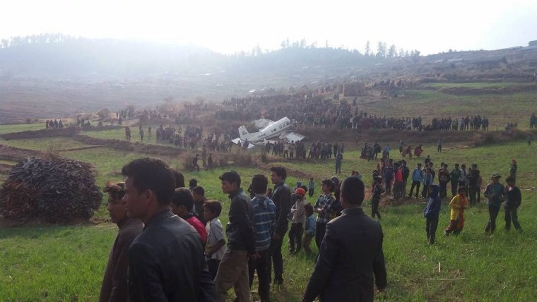 Image: People gather around the crash site of a small plane operated by Kasthamandap Airlines in Kalikot