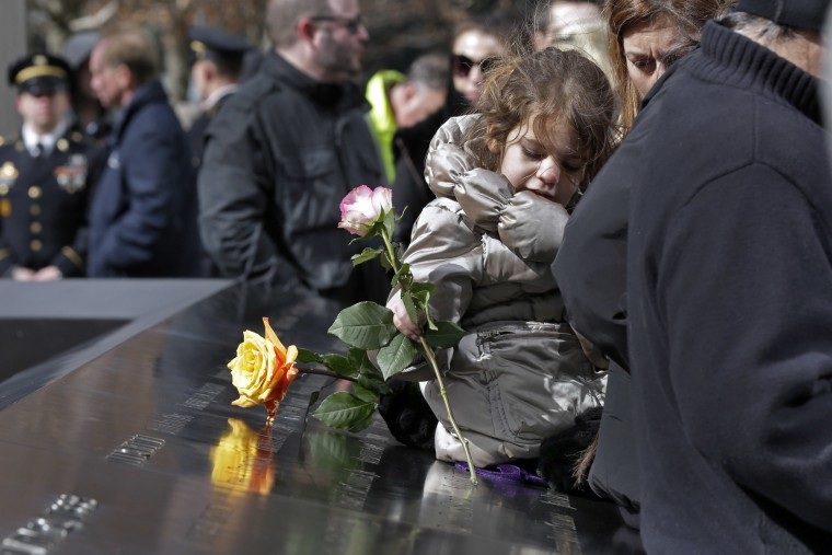 Image: A young girl places a rose at the 9/11 Memorial during a ceremony commemorating the 23rd anniversary of the 1993 World Trade Center bombing