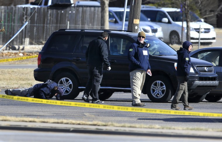 Image: FBI agents search the parking lot at Excel Industries