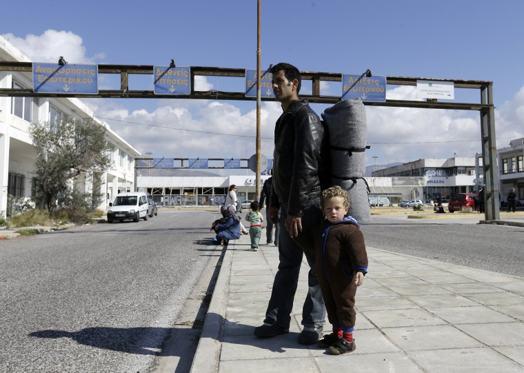 Image: A man holds a child at Athen's old international airport