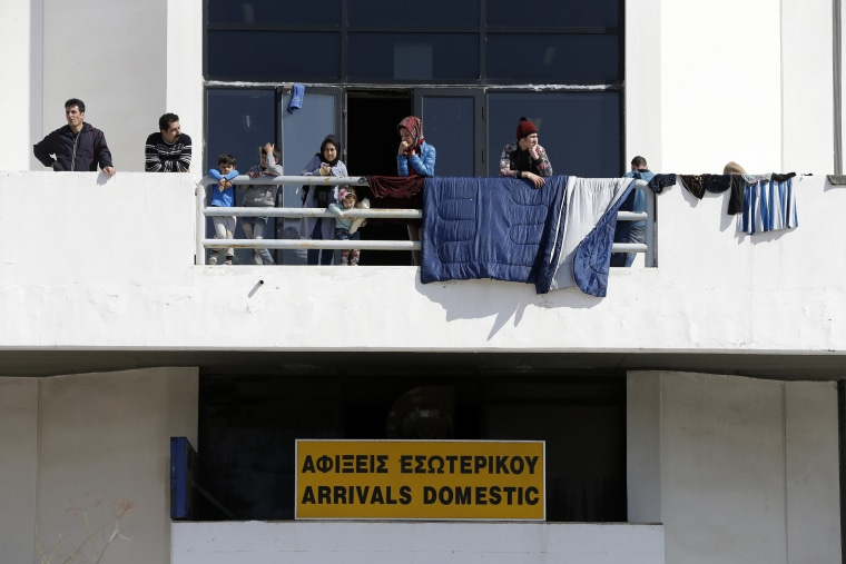 Image: People stand on a balcony of Athens' old international airport