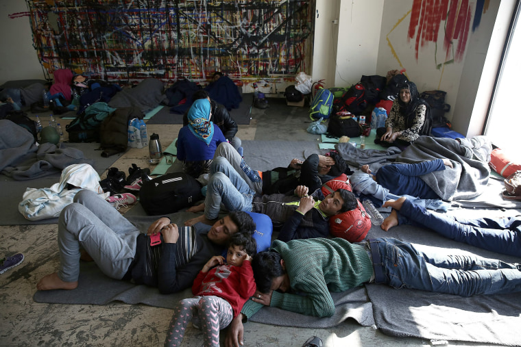 Image: Migrants rest inside the old Athens airport