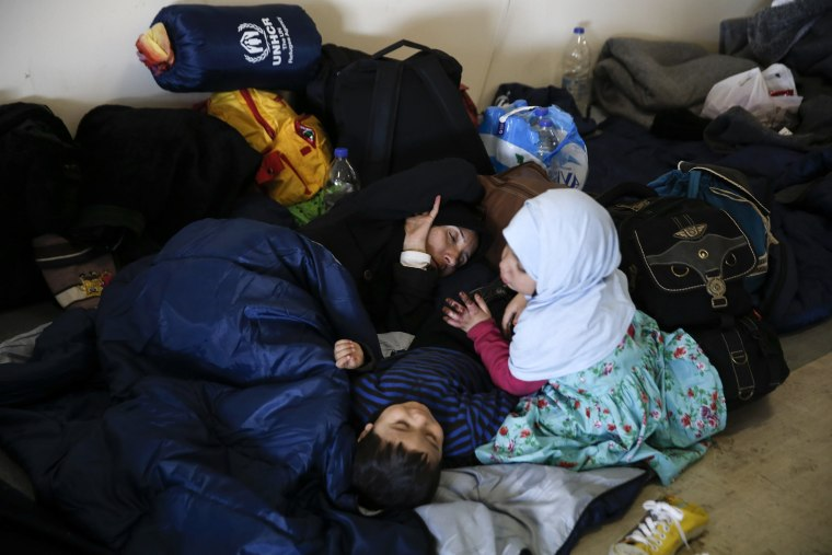 Image: A migrant woman sleeps as her children play next to her inside the disused Hellenikon airport