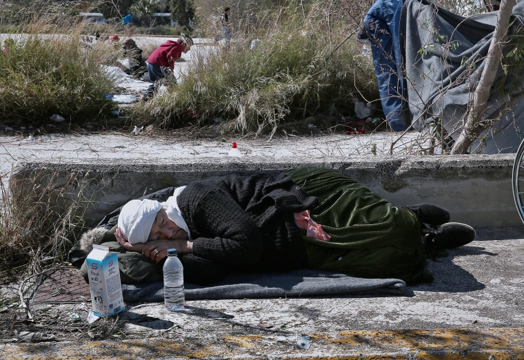Image: An elderly migrant sleeps on the ground outside the old airport