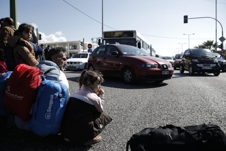 Image: Protesting stranded refugees and migrants block a highway next to the disused Hellenikon airport