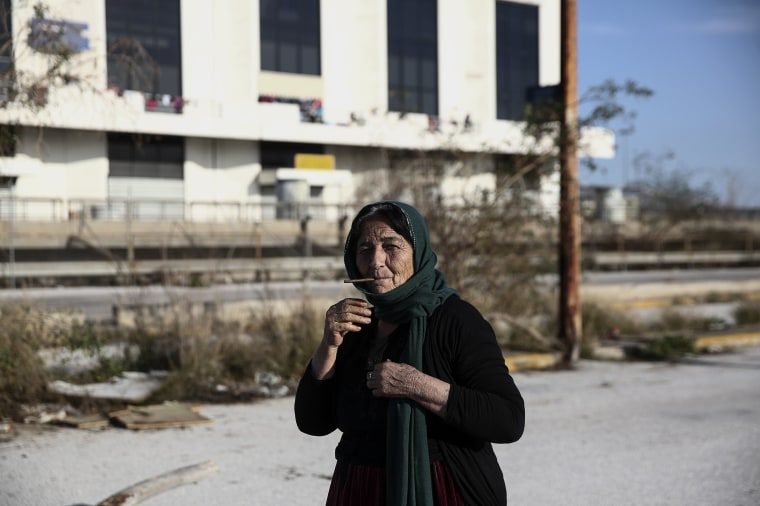 Image: A woman smokes a cigarette outside the old international airport