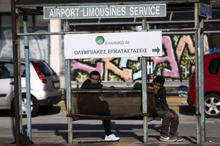 Image: Two youths sit at an abandoned limousine stop outside the old international airport