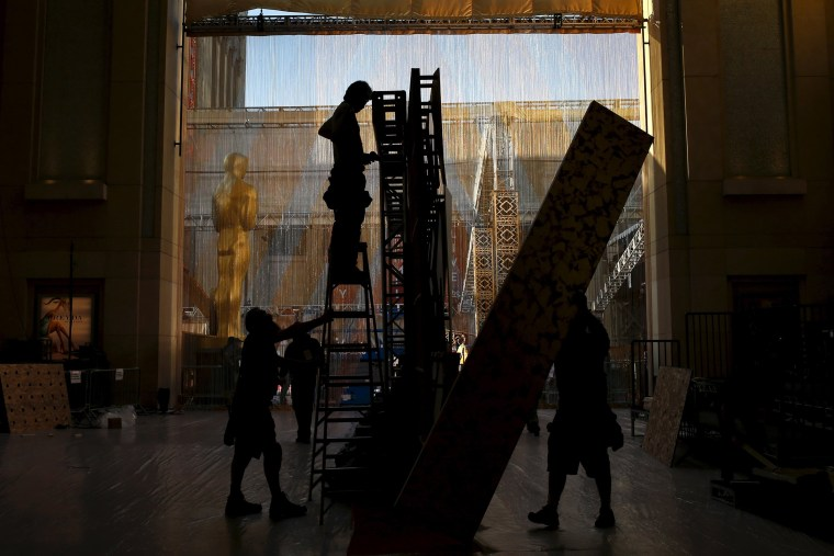 Image: Workers set panels for a backdrop along the red carpet at the Dolby Theatre, the site for the 88th Academy Awards in Hollywood