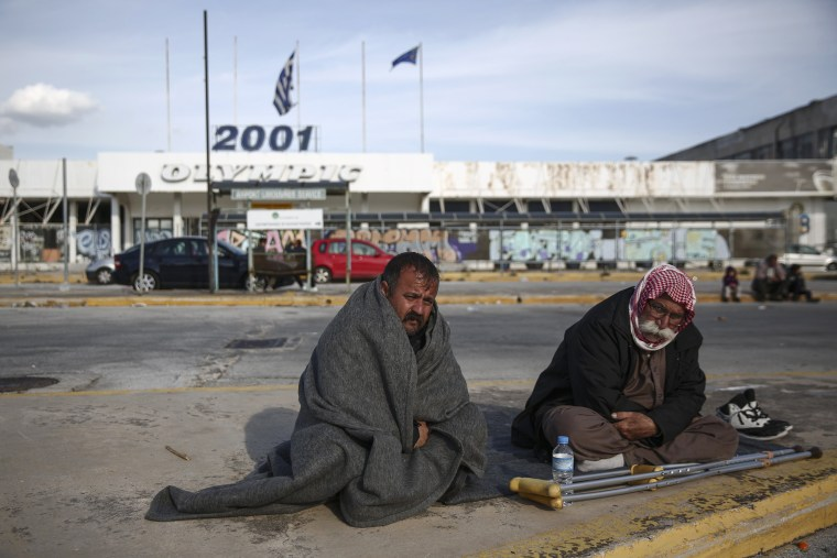 Image: Two men from Iraq sit at a parking area outside the old international airport in Athens
