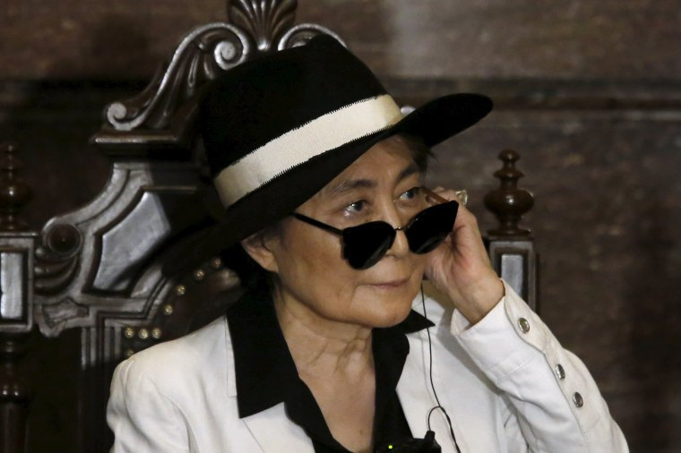 Image: Artist Yoko Ono listens through an earpiece before she was honored as 'Illustrious Visitor