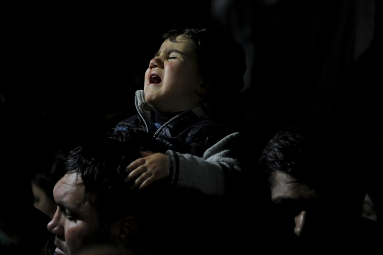 Image: A baby cries during a protest by stranded refugees at the Greek-Macedonian border who wait for the border crossing to reopen near the Greek village of Idomeni