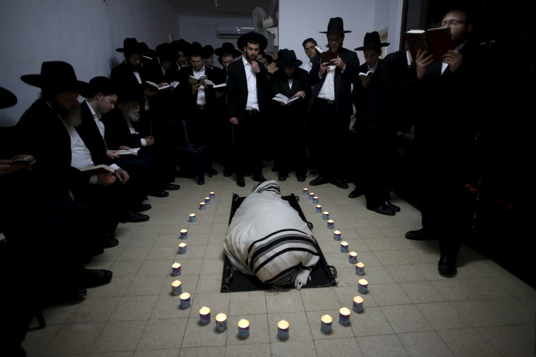 Image: Candles surround the body of Rabbi Chaim Shlomo Leibowitz, head of the Ponevezh Yeshiva, before his funeral at his home in Bnei Brak