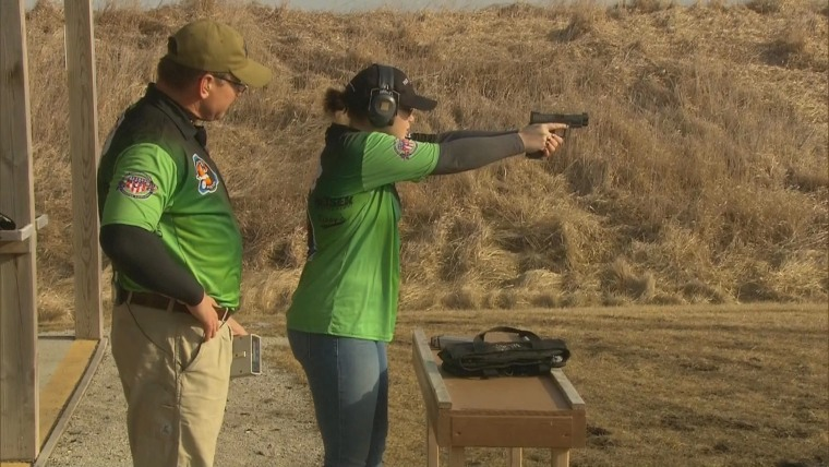 Grace Hood, age 16, conducts a rapid fire practice with a semi-automatic handgun, while her father observes at a gun range near Elkhart, Iowa on Thursday, Feb. 25th.