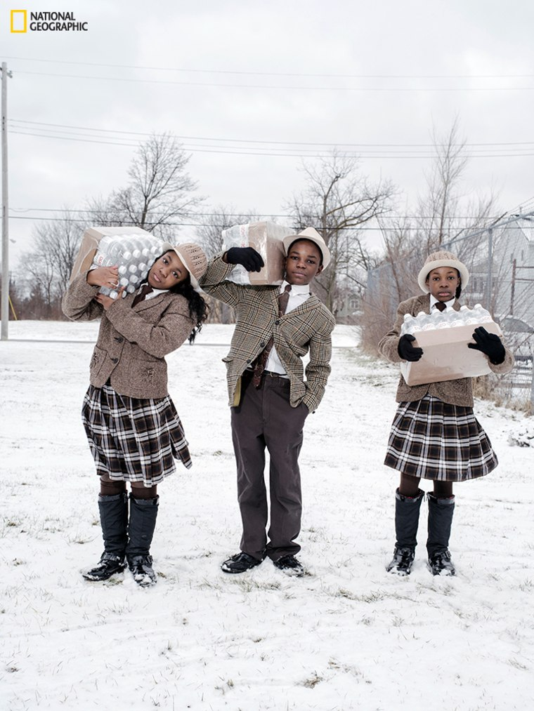 Siblings Julie, Antonio, and India Abram collect their daily allowance of bottled water from Fire Station #3. Located on Martin Luther King Avenue, it is one of five firehouses that have become water resource sites in Flint, Michigan.