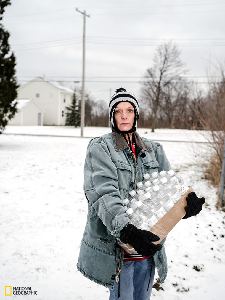 Julie Bennett poses with her daily case of water from Firehouse #3 on Martin Luther King Avenue on Jan. 27.