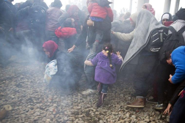 Image: Migrants run after Macedonian police fired tear gas near the northern Greek village of Idomeni Monday.
