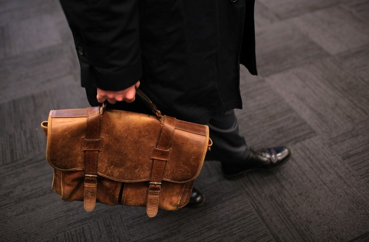 Image: A job seeker carries a worn briefcase