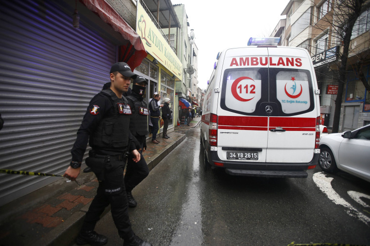 Image: Police officers stand stand next to an ambulance following an attack at the entrance to police station in Bayrampasa