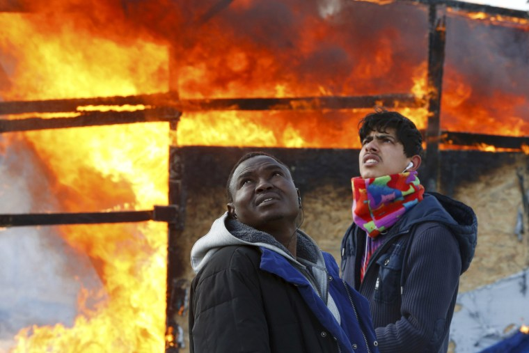 "Image: Migrants stand next to a burning makeshift shelter during the dismantlement of the migrant shanty town called the ""Jungle"" in Calais"