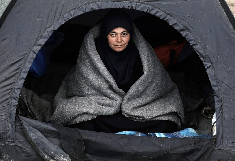 A refugee sits in a tent covered with a blanket during a rainy day in a field outside the refugee camp in Idomeni, northern Greece. At least 10,000 Syrian and Iraqi refugees have been waiting for days at the Idomeni crossing on Greece's border with Macedonia, in an official shelter and in tents that they set up in the fields.