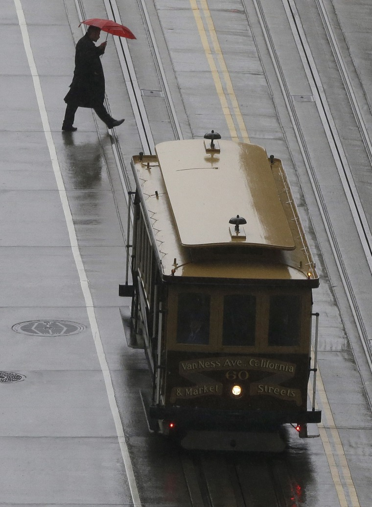 A pedestrian crosses the street behind a cable car Friday in San Francisco.