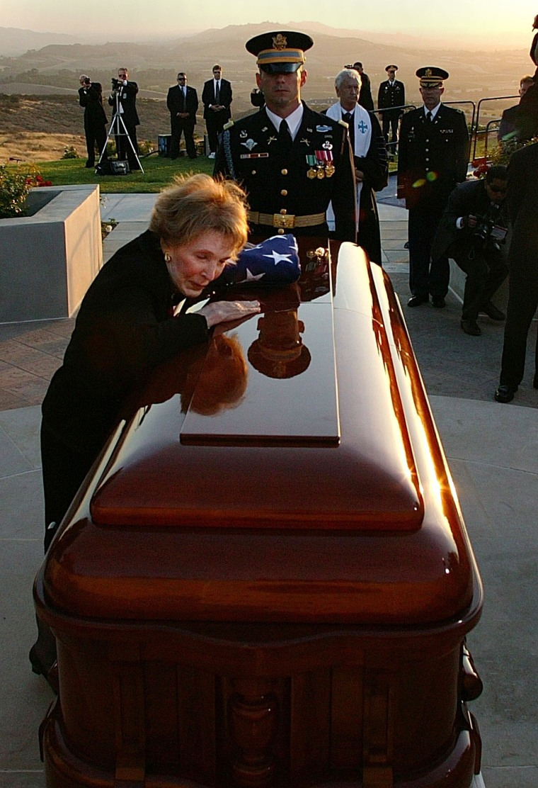 Image: Nancy Reagan leans into the casket of her husband during the interment ceremony