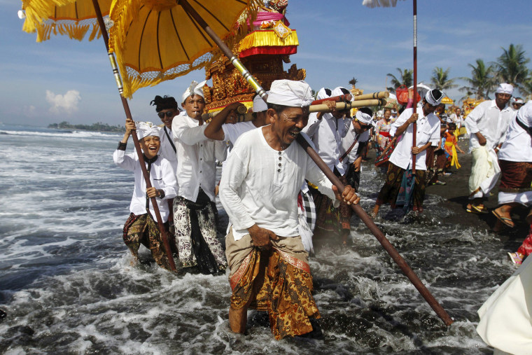 Image: Balinese Hindus carry Pratimas, or symbols of God, on the beach during Melasti, a purification ceremony, ahead of the holy day of Nyepi, in Gianyar