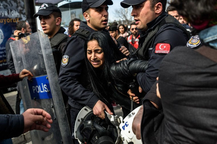 Image: Turkish anti riot police officers detain a woman