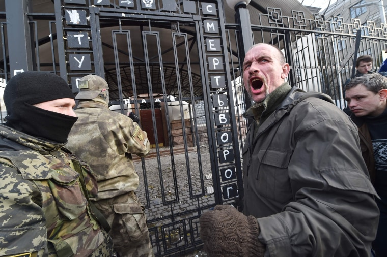 Image: A protester shouts in front of the Russian embassy in Kiev