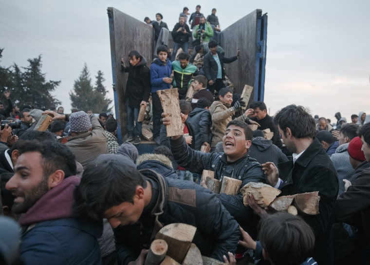 Image: Migrants mob a truck bringing donated firewood at the northern Greek border station of Idomeni