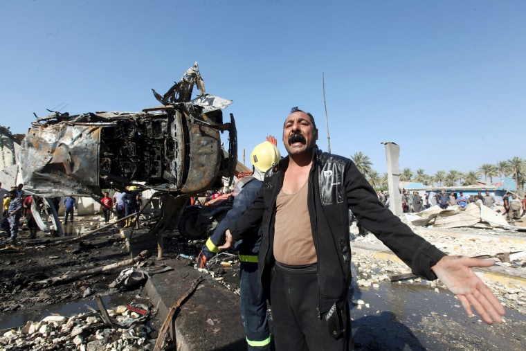 Image: A man reacts at the site of a bomb attack at a checkpoint in the city of Hillah