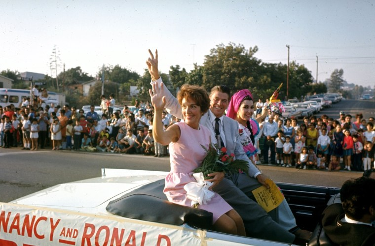 Image: Nancy rides in a convertible with her husband