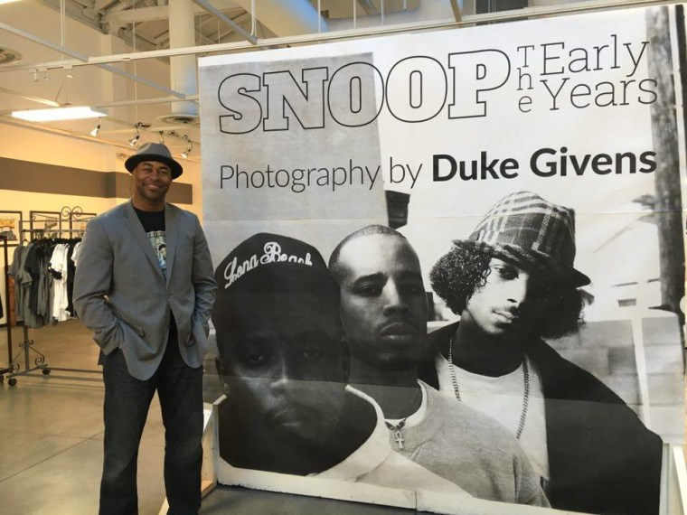 "Duke givens stands next to a sign for his ""SNOOP THE EARLY YEARS"" exhibit"