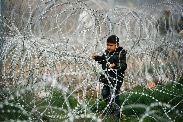 Image: A child stands among a razor-topped fence close to the gate at the Greek-Macedonian border