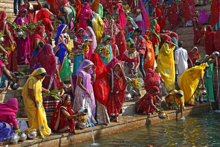 Image: Hindu women collect water from the Pushkar lake to pour on idols of Lord Shiva