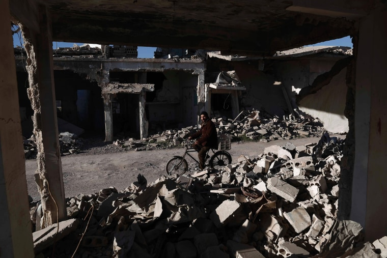 Image: A Syrian man rides his bicycle past the rubble of destroyed buildings